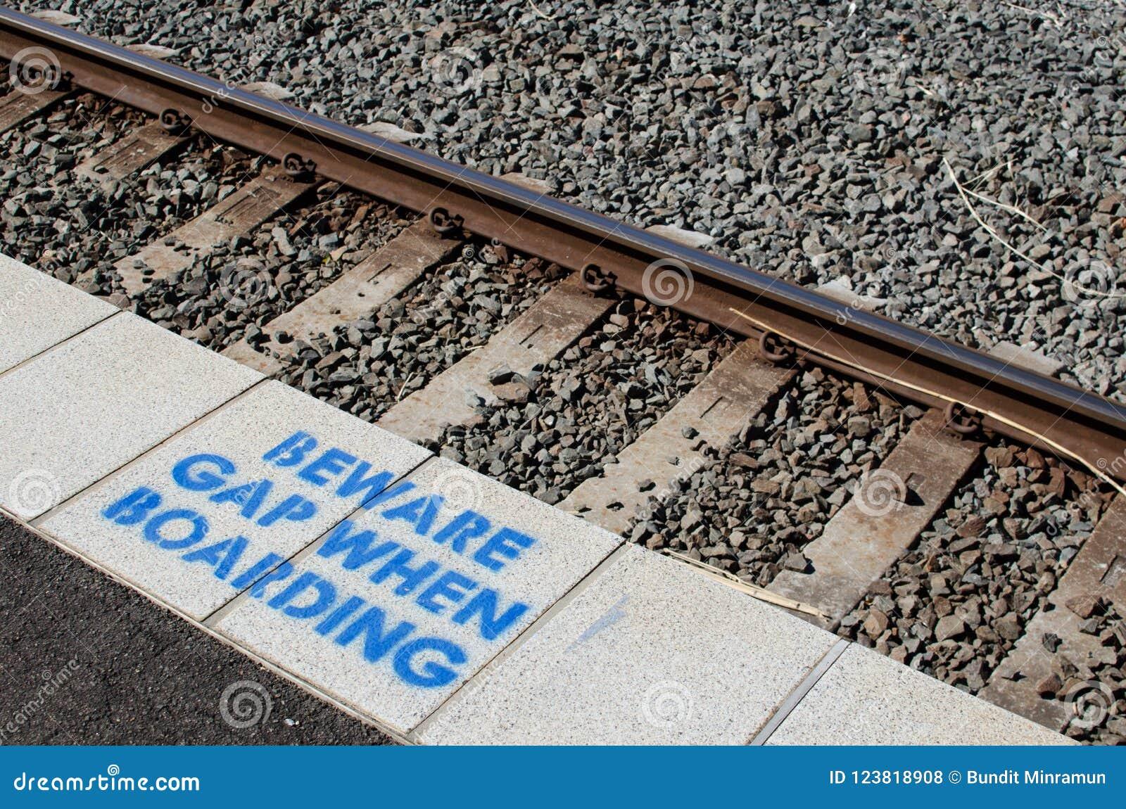 Znak ostrzegawczy przy stacją kolejową dla wystrzega się przerwę gdy wsiadający obraz na platformie