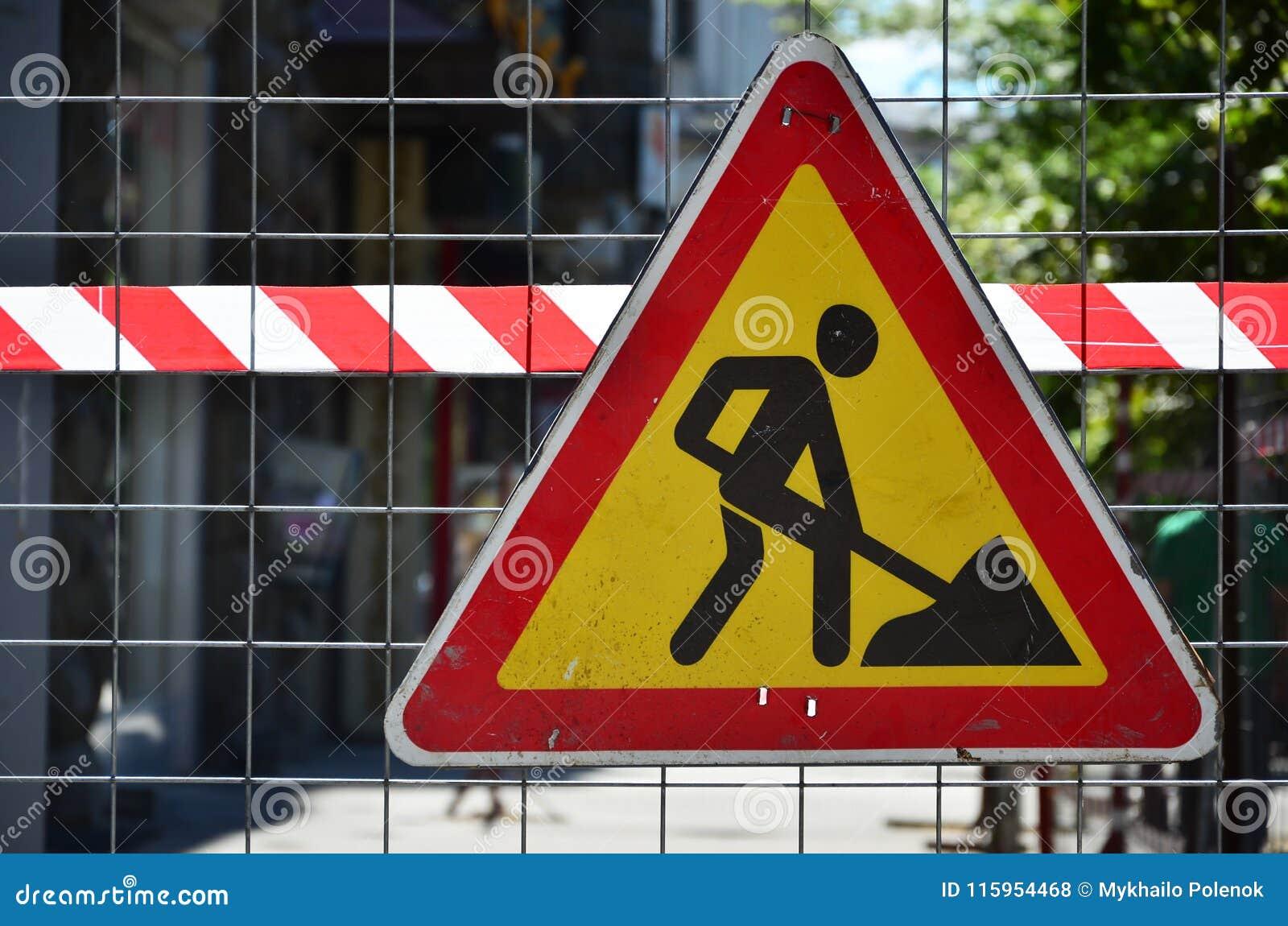 Znaka ostrzegawczego ` w budowie ` dołącza metal siatki ogrodzenie z czerwonym i biel paskującym sygnału klepnięciem