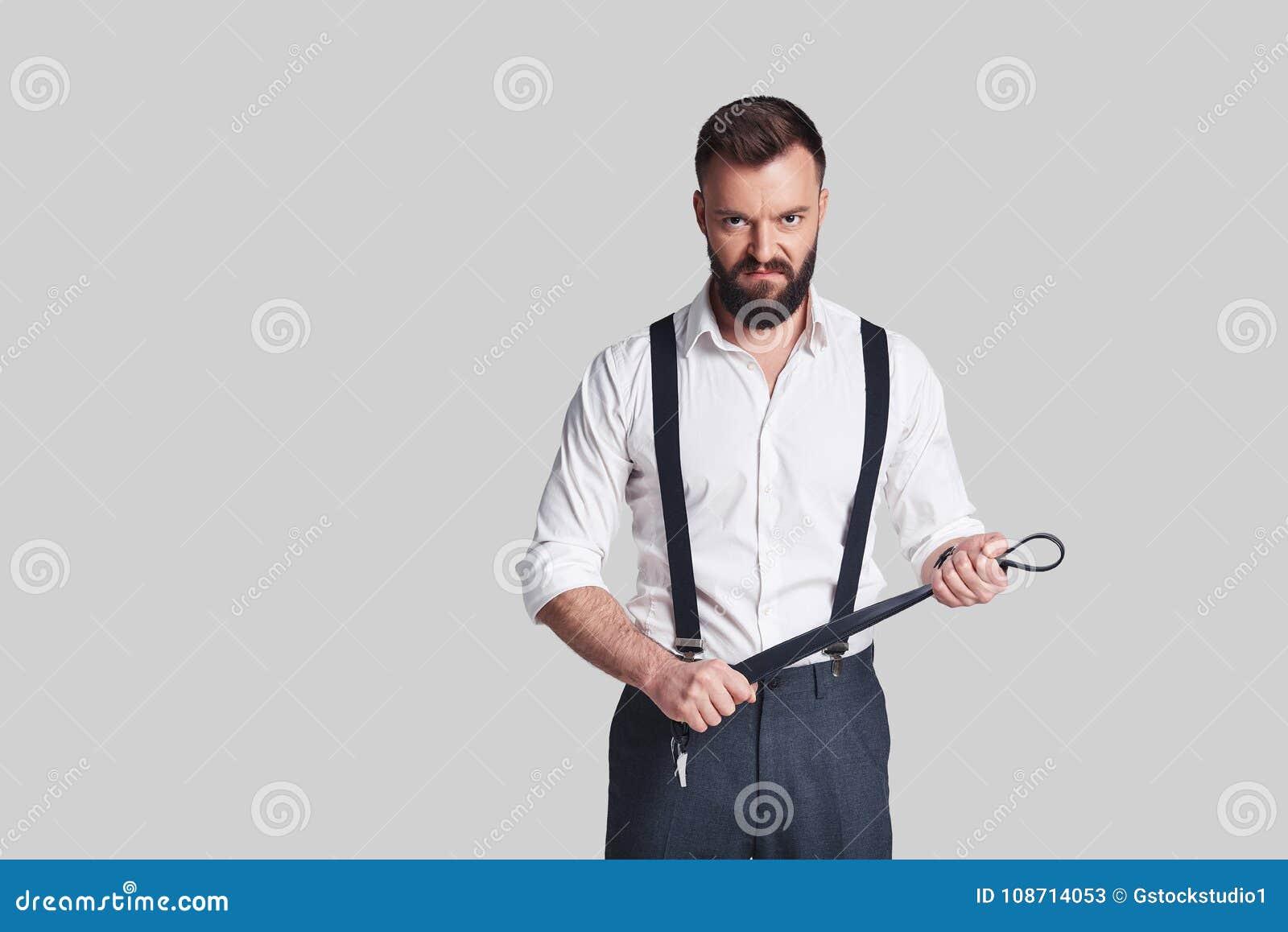 Zo wreed! De boze jonge mens in formalwear dragend een riem en kijkt