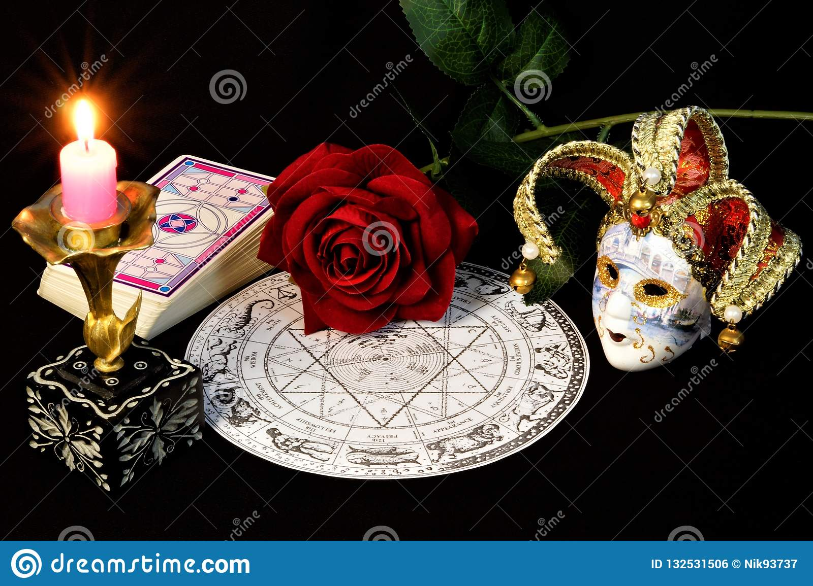 Zodiac horoscope, bright candle, red rose, Queen of flowers, cards for predictions, carnival jester mask, symbol of transformation
