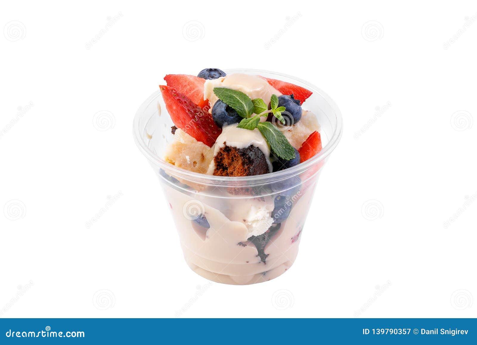 Zoet dessert met koekje, bessen en slagroom die op witte achtergrond wordt geïsoleerd Heerlijk die dessert wordt verfraaid met