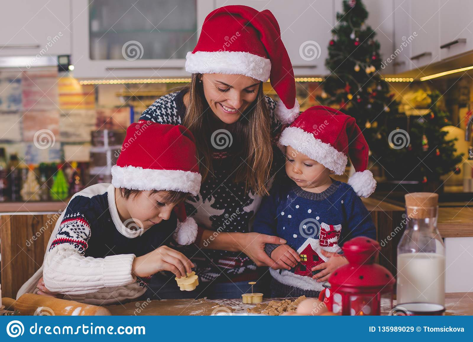Zoet peuterkind en zijn oudere broer, jongens, die mama helpen die Kerstmiskoekjes thuis voorbereiden