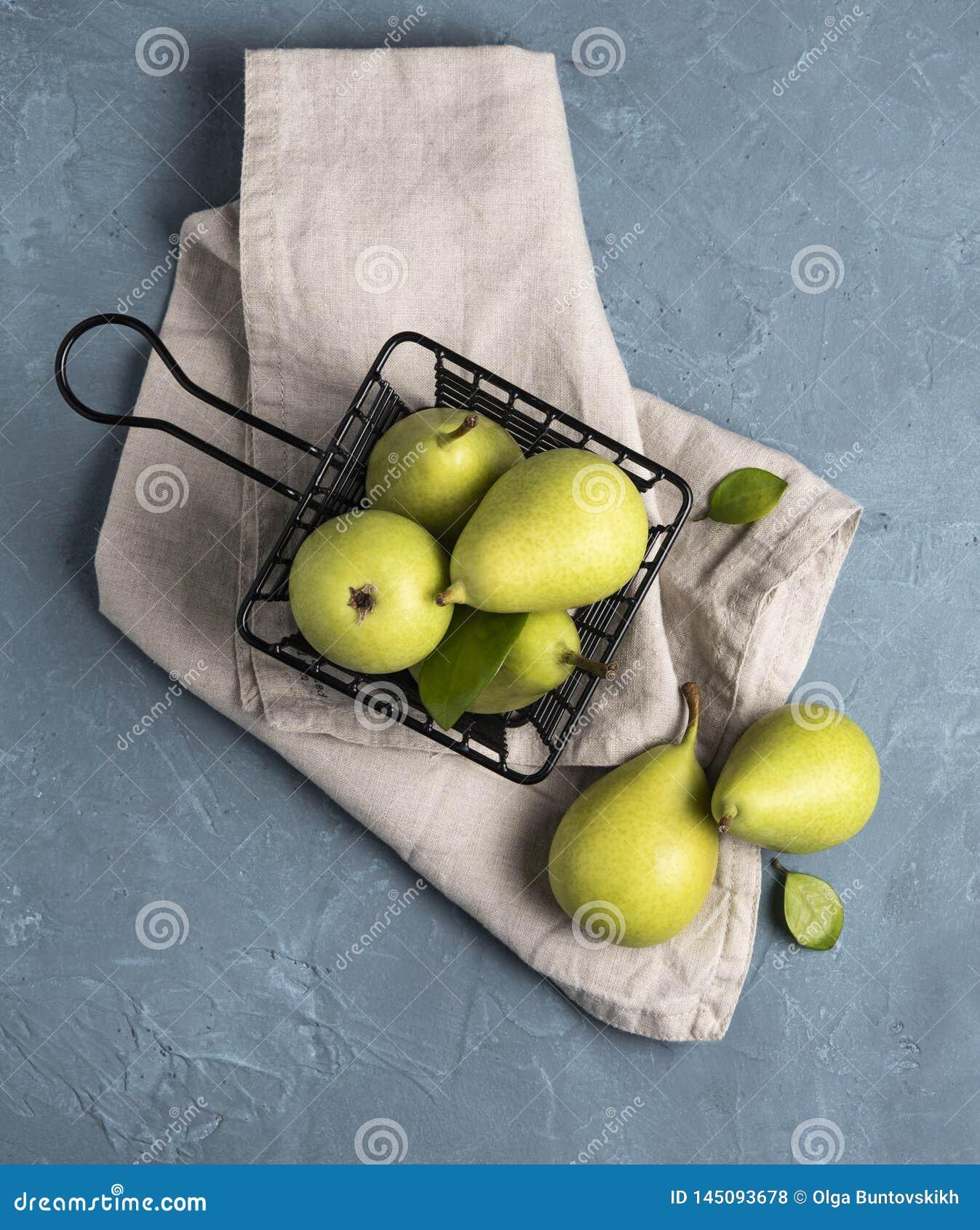 Zoete heerlijke groene peren binnen zwarte mand op het blauwe lijstfruit