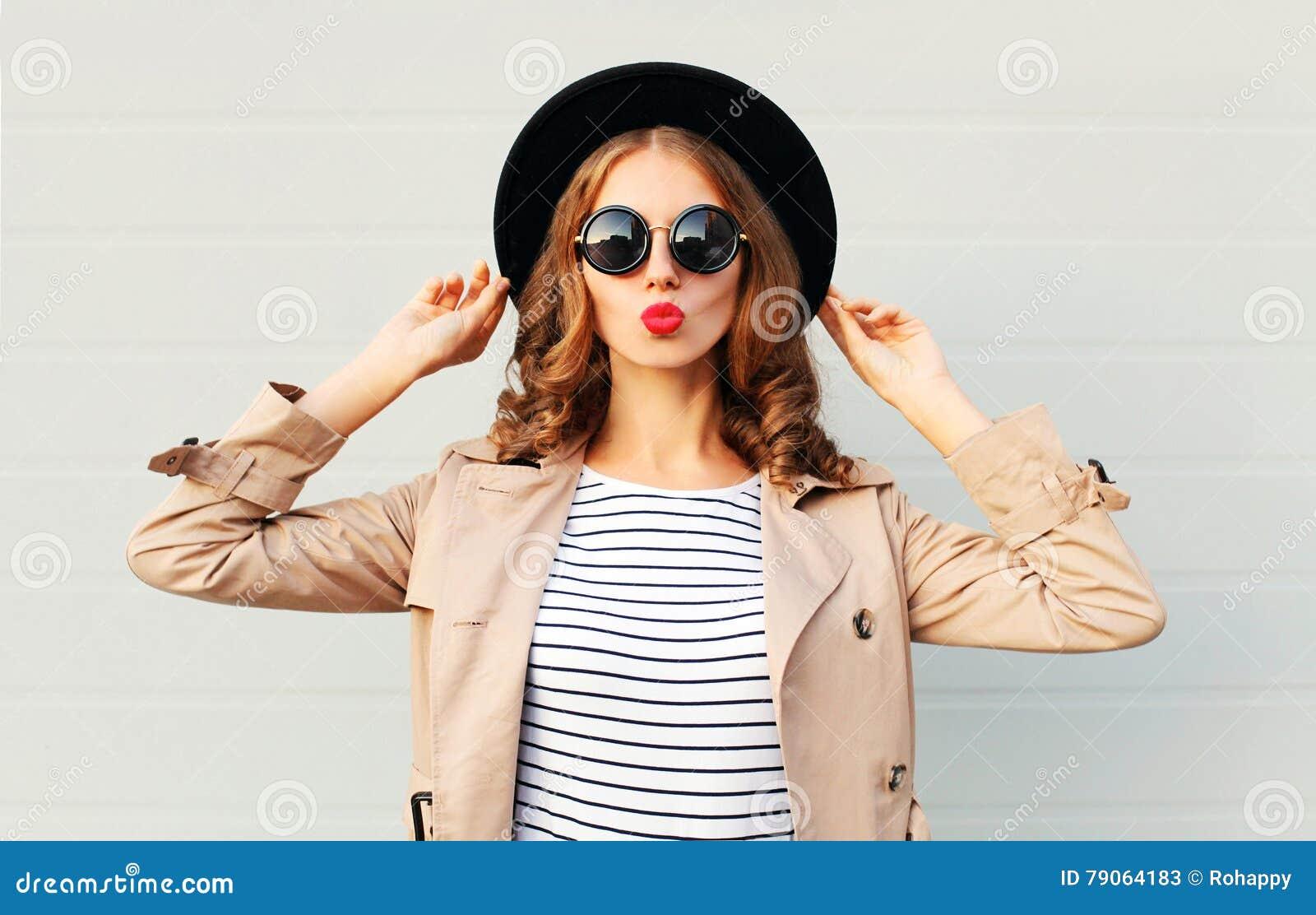 Zoete jonge vrouw die van het manierportret de vrij rode lippen blazen die een zwarte laag van de hoedenzonnebril over grijs drag