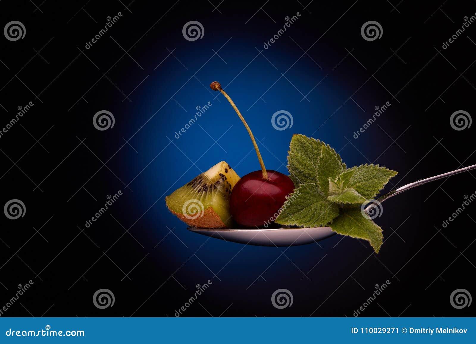 Zoete kers en kiwi op een lepel