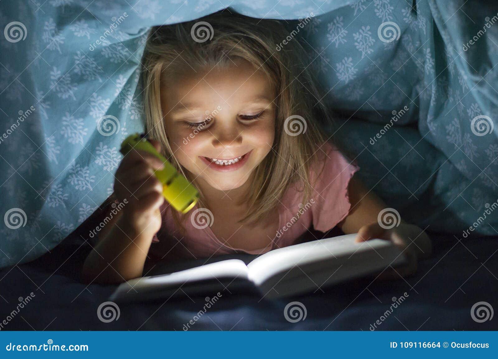 Zoete mooi en mooi weinig blond meisje 6 tot 8 jaar oud onderbed behandelt lezingsboek in dark bij nacht met toortslicht