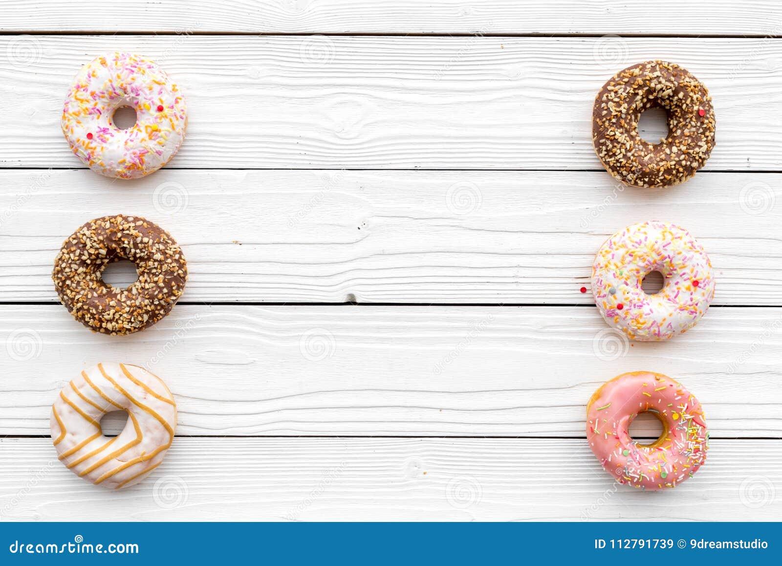 Zoete smakelijke snack Verglaasde doughnut op de witte houten ruimte van het achtergrond hoogste meningsexemplaar