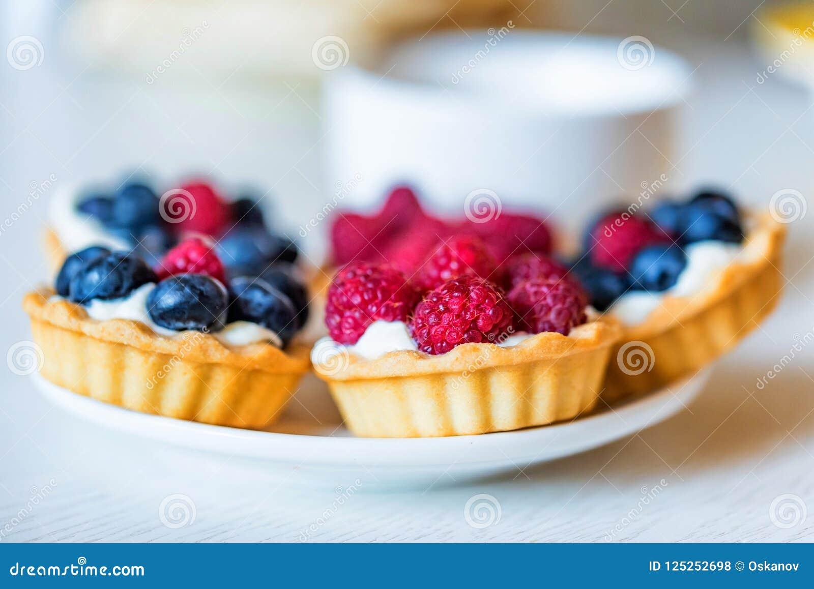 Zoete taartjes met gemengde bessen op een plaat