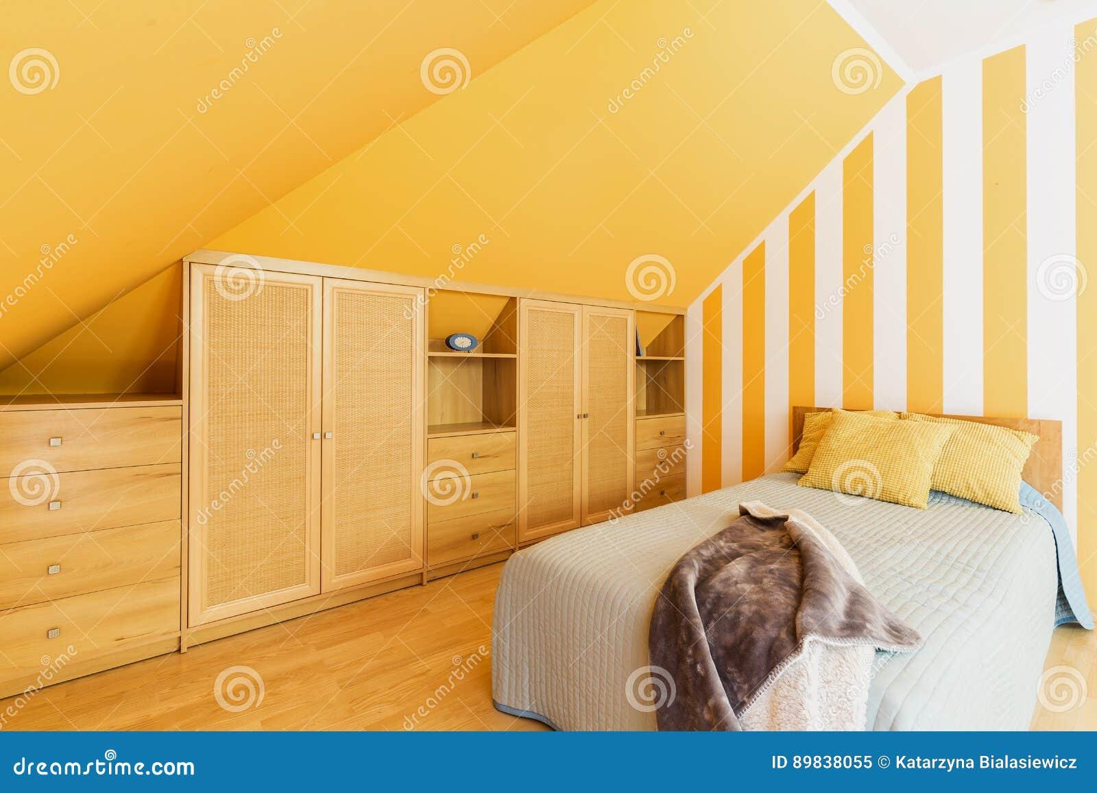 Gele Muur Slaapkamer : Zolderslaapkamer met intense gele muren stock afbeelding