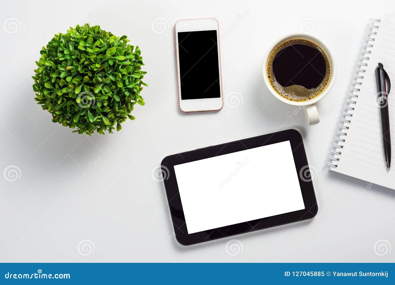 Zombe acima da mesa de escritório com o PC branco vazio da tabuleta da tela, o potenciômetro preto do smartphone da tela da placa