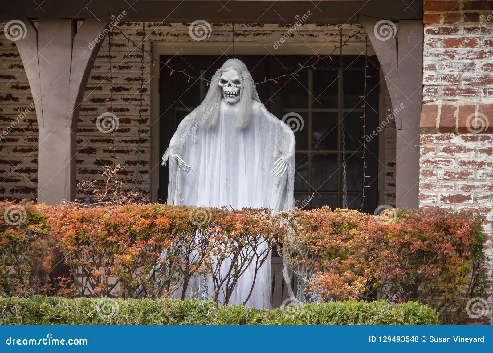 Zombiespook die zich op portiek achter de herfst gekleurde haag voor Halloween-decoratie bevinden