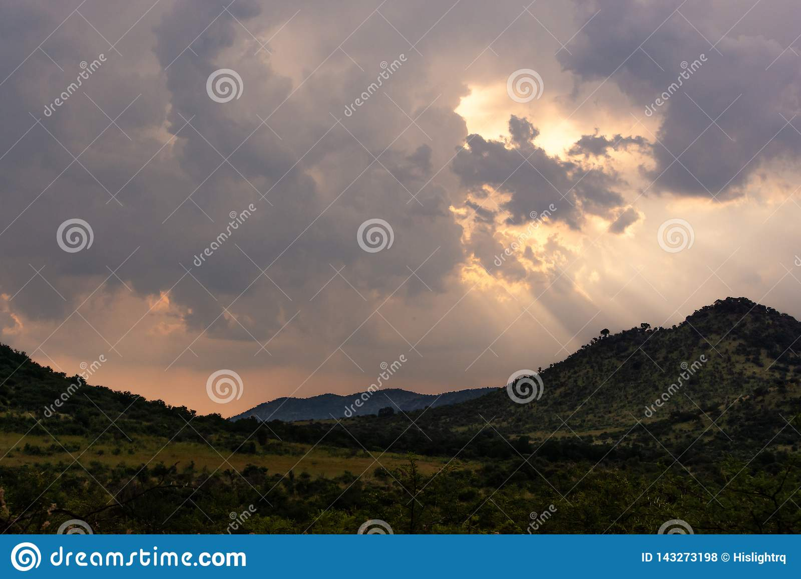 Zon het breken door onweerswolken over Afrikaanse savanne