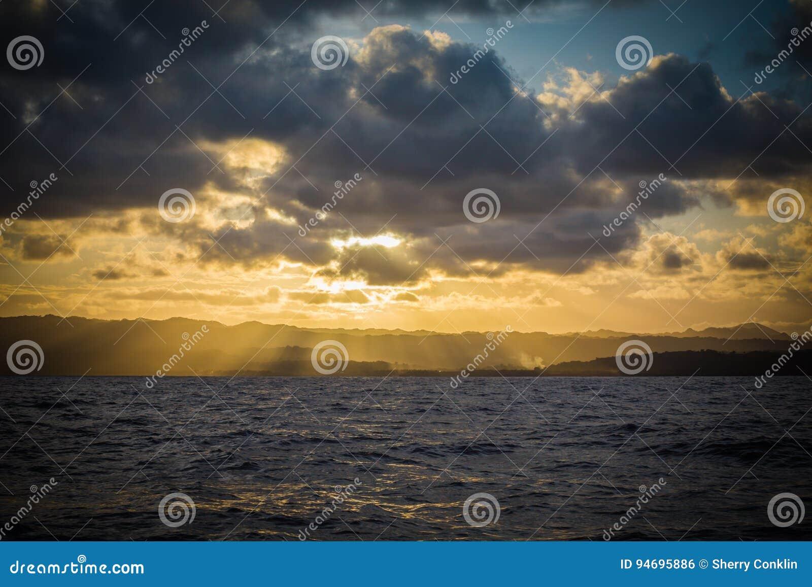 Zon over eilandbergen wordt geplaatst van de oceaan die