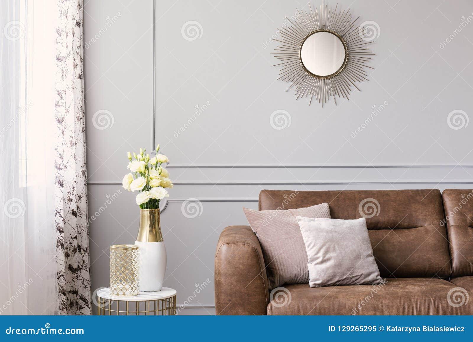 Zon zoals gevormde spiegel boven leerbank met hoofdkussens in grijze elegante woonkamer