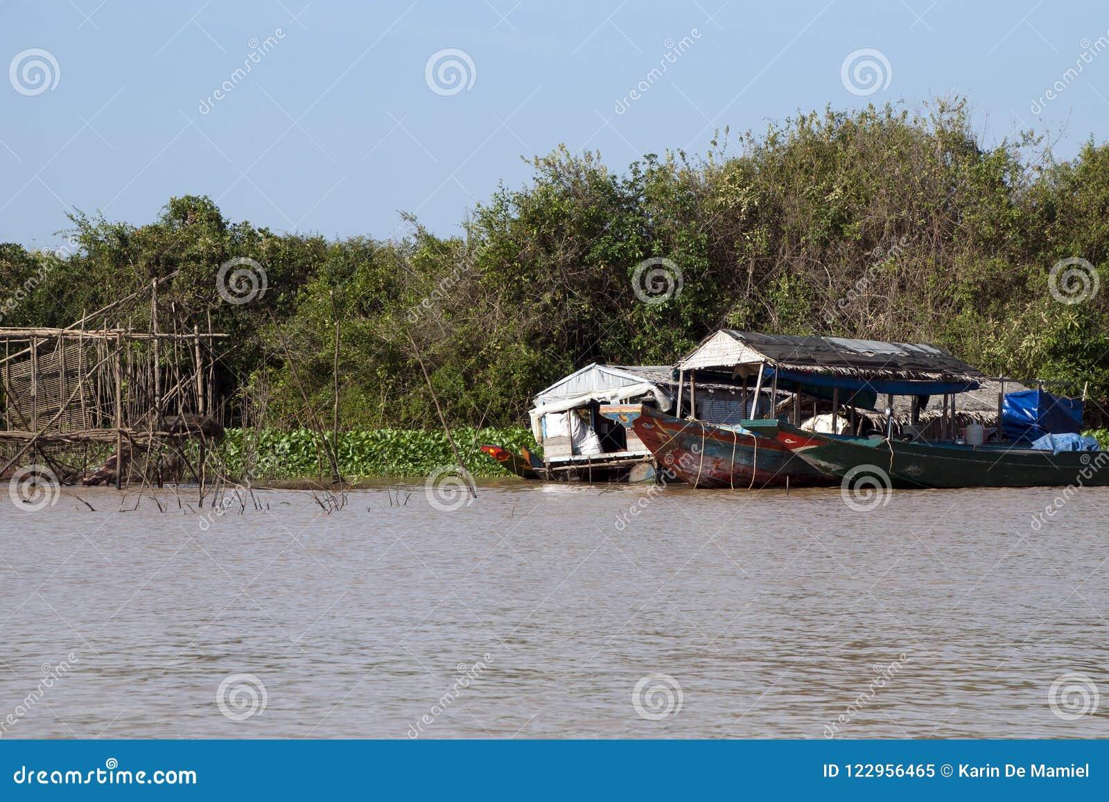 Zone inondable de lac sap de Tonle avec le bateau-maison près d une structure en bois de pêche