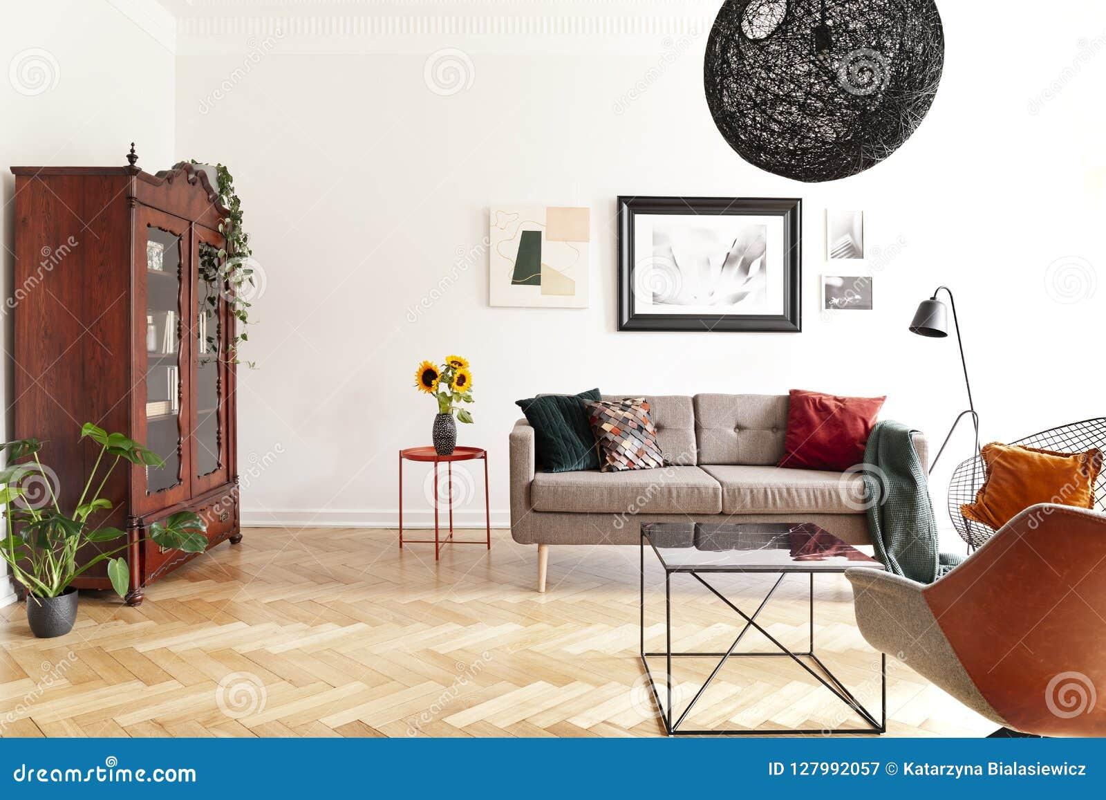 Zonnebloemen op lijst naast bank in helder woonkamerbinnenland met affiches en installaties Echte foto