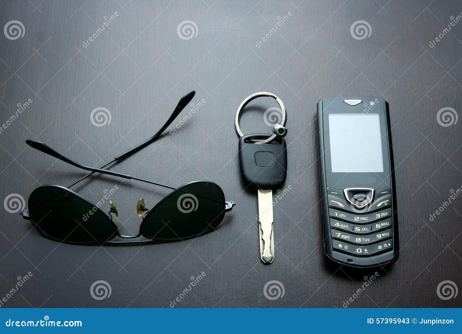 Zonnebril, autosleutel en cellphone op een houten lijst