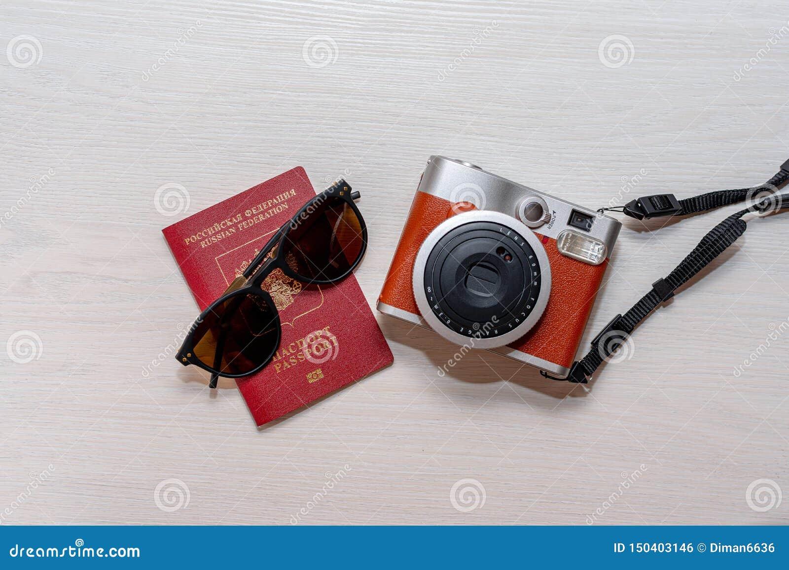 Zonnebril met het paspoort van een burger van de Russische Federatie en een onmiddellijke fotocamera op een witte houten achtergr