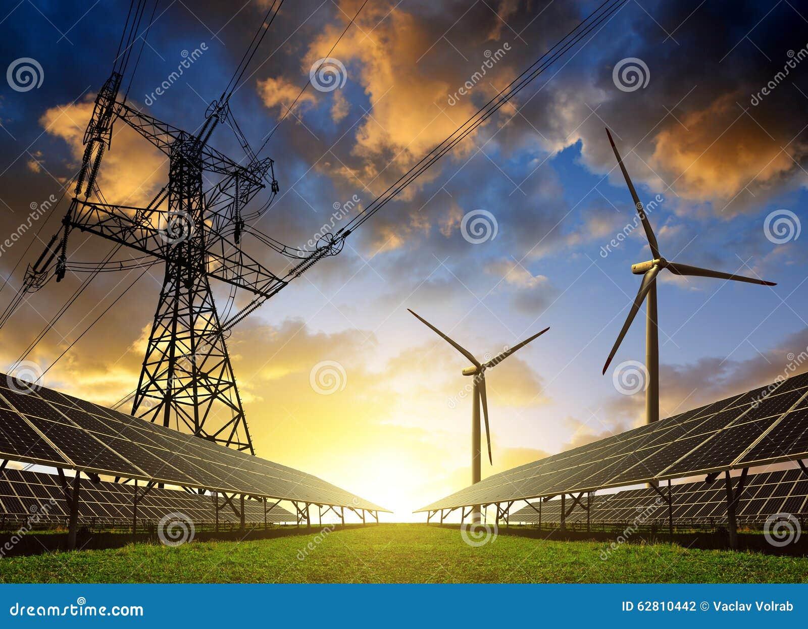 Zonnepanelen met windturbines en elektriciteitspyloon bij zonsondergang