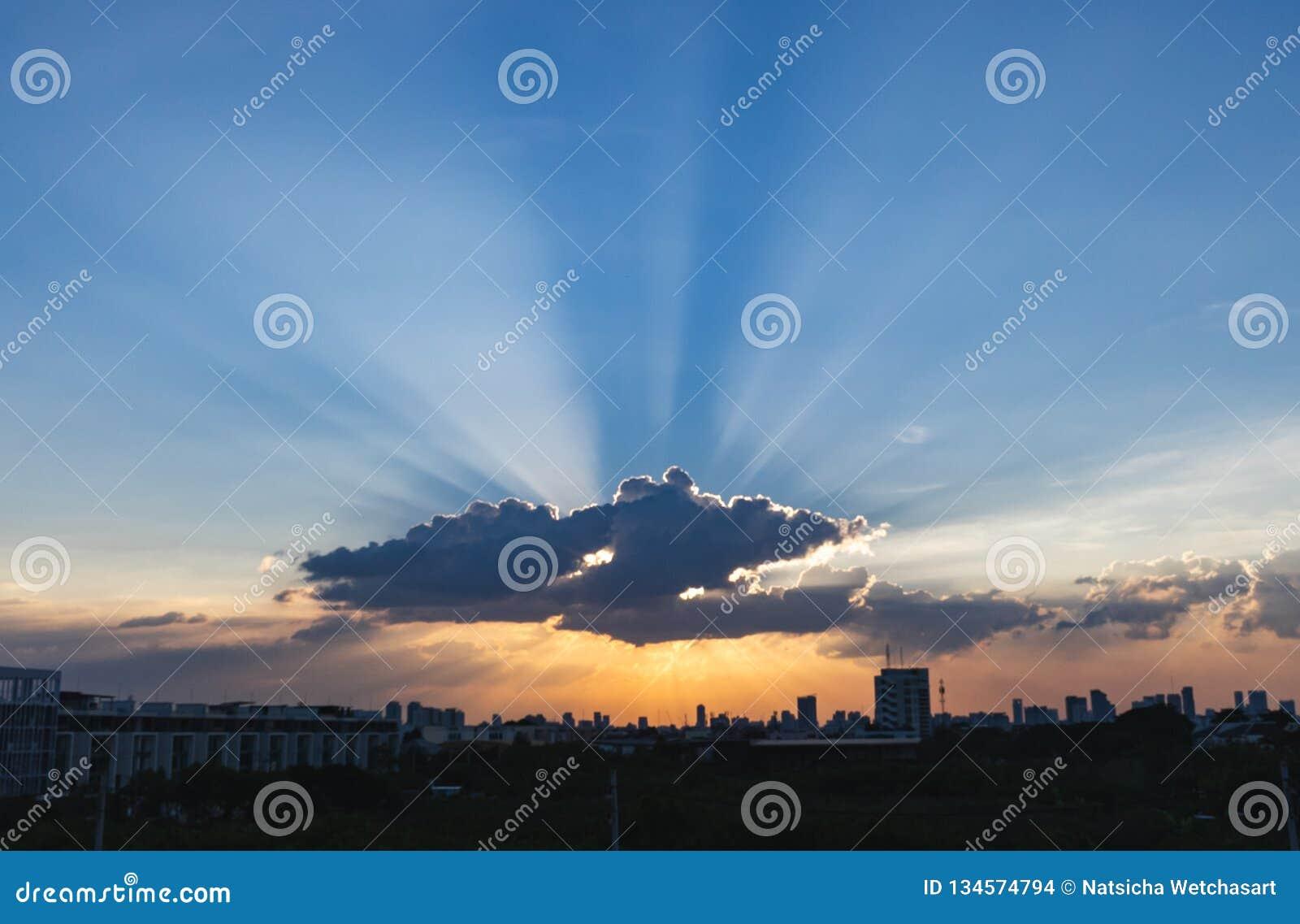 Zonnestraal door de dramatische wolk tijdens zonsondergangtijd, met de silhueetebouw op achtergrond