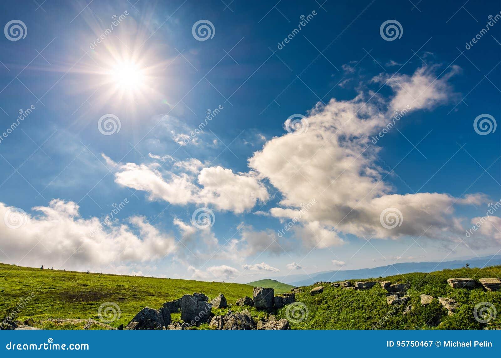 Zonnestraal op een blauwe hemel met wolken over de bergen