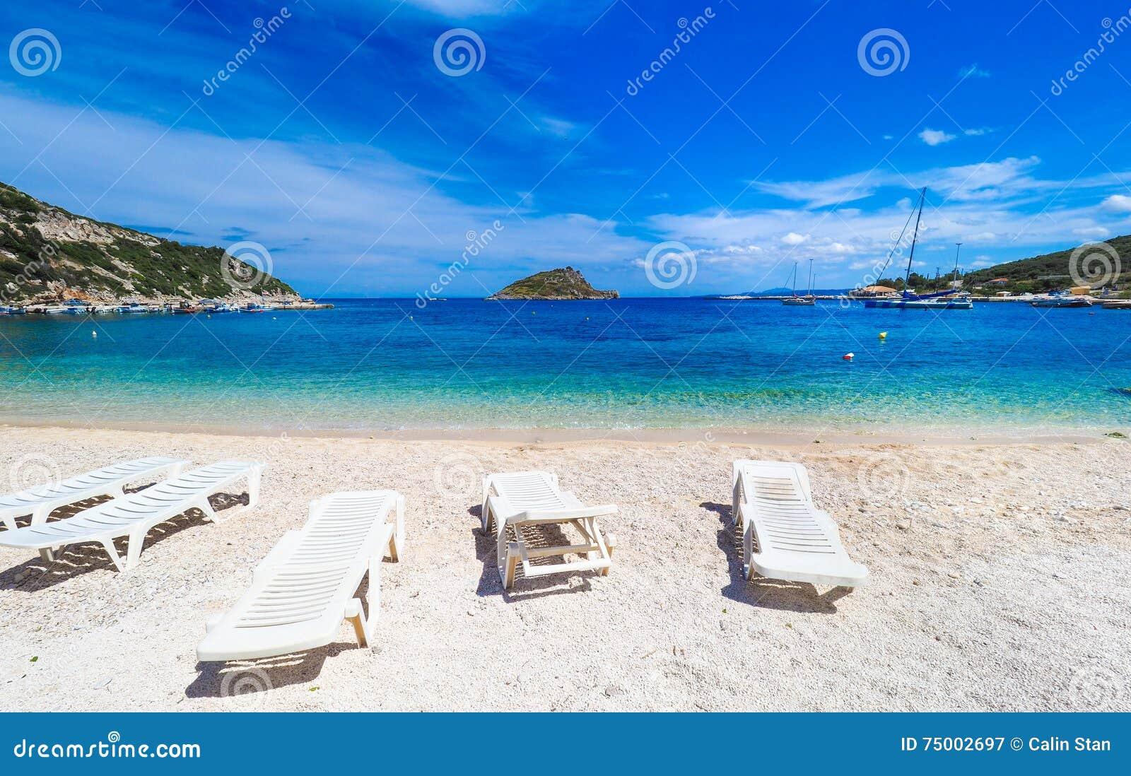 Zonnig de zomerstrand in Griekenland met zonbedden en kleine boot