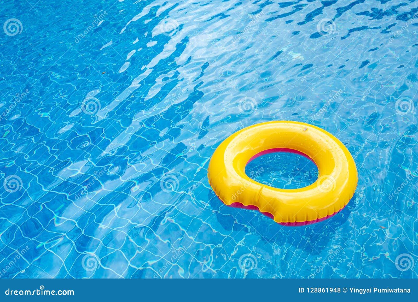 Zonnige dag bij de pool Heldere gele vlotter in blauw zwembad,