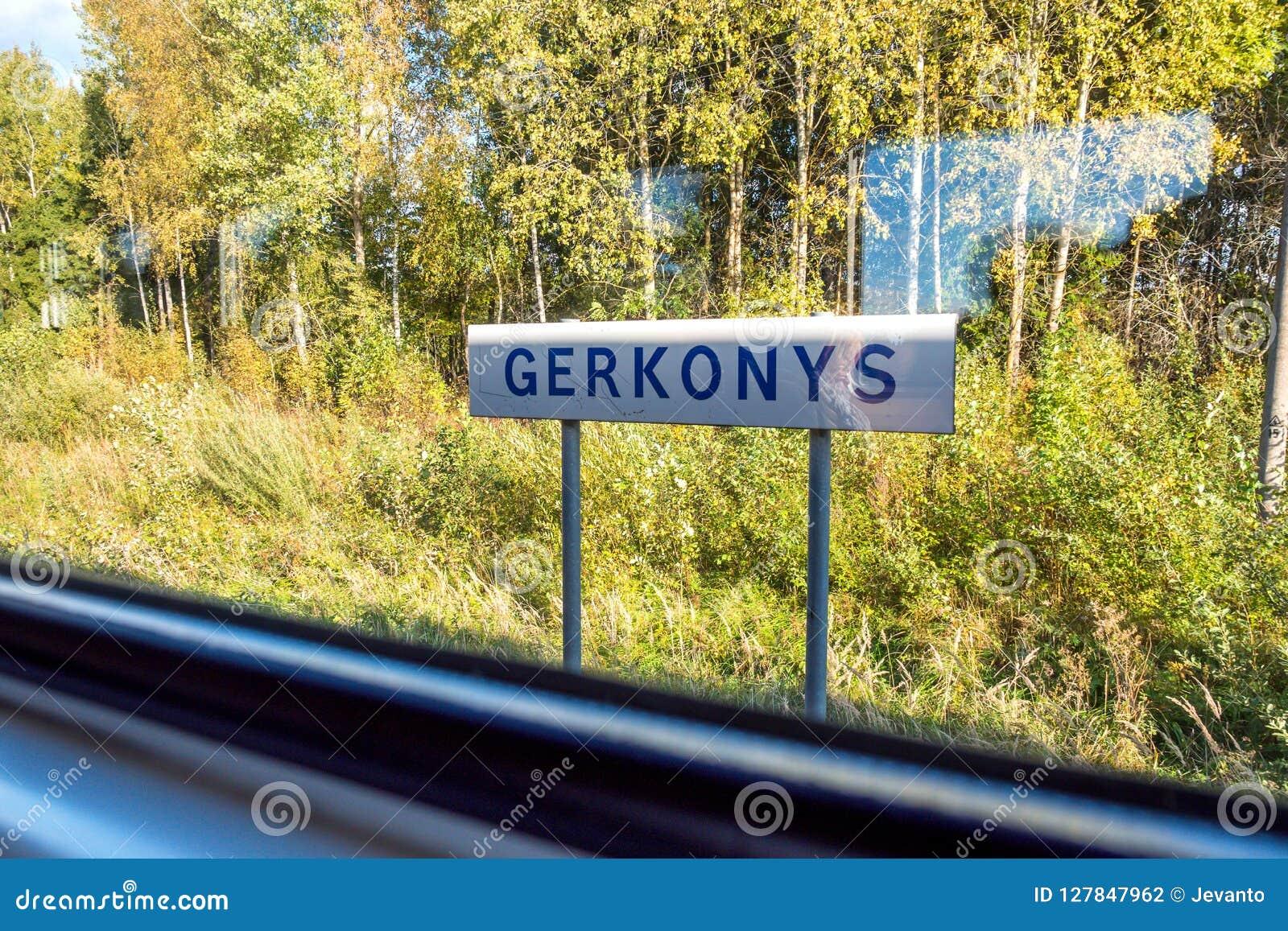 Zonnige dagmening van Gerkonys-stadsnaambord door treinvenster die van visaginas naar vilnius Litouwen reizen