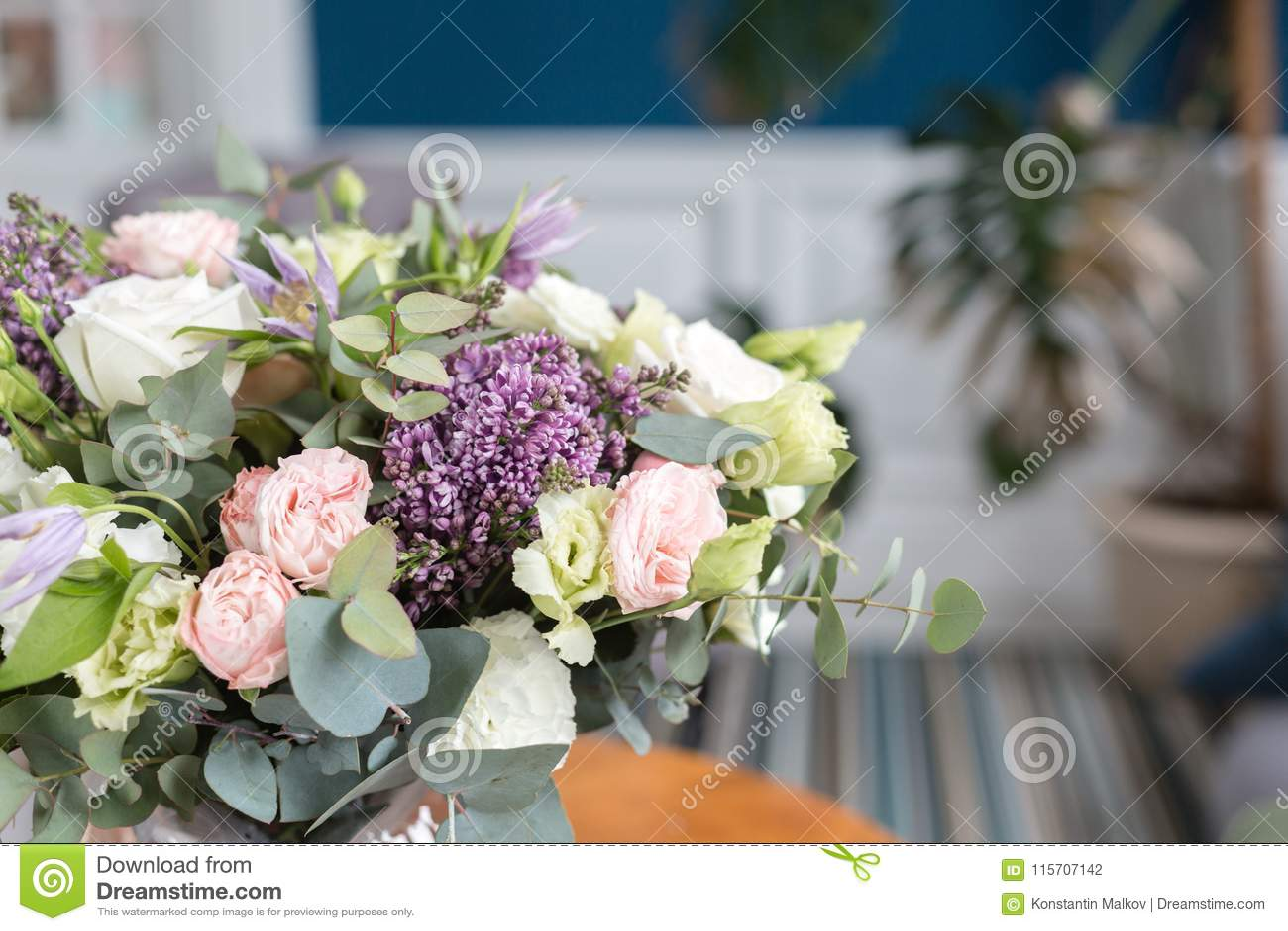 Zonnige de lenteochtend in woonkamer Mooi luxeboeket van gemengde bloemen in glasvaas op houten lijst Het werk