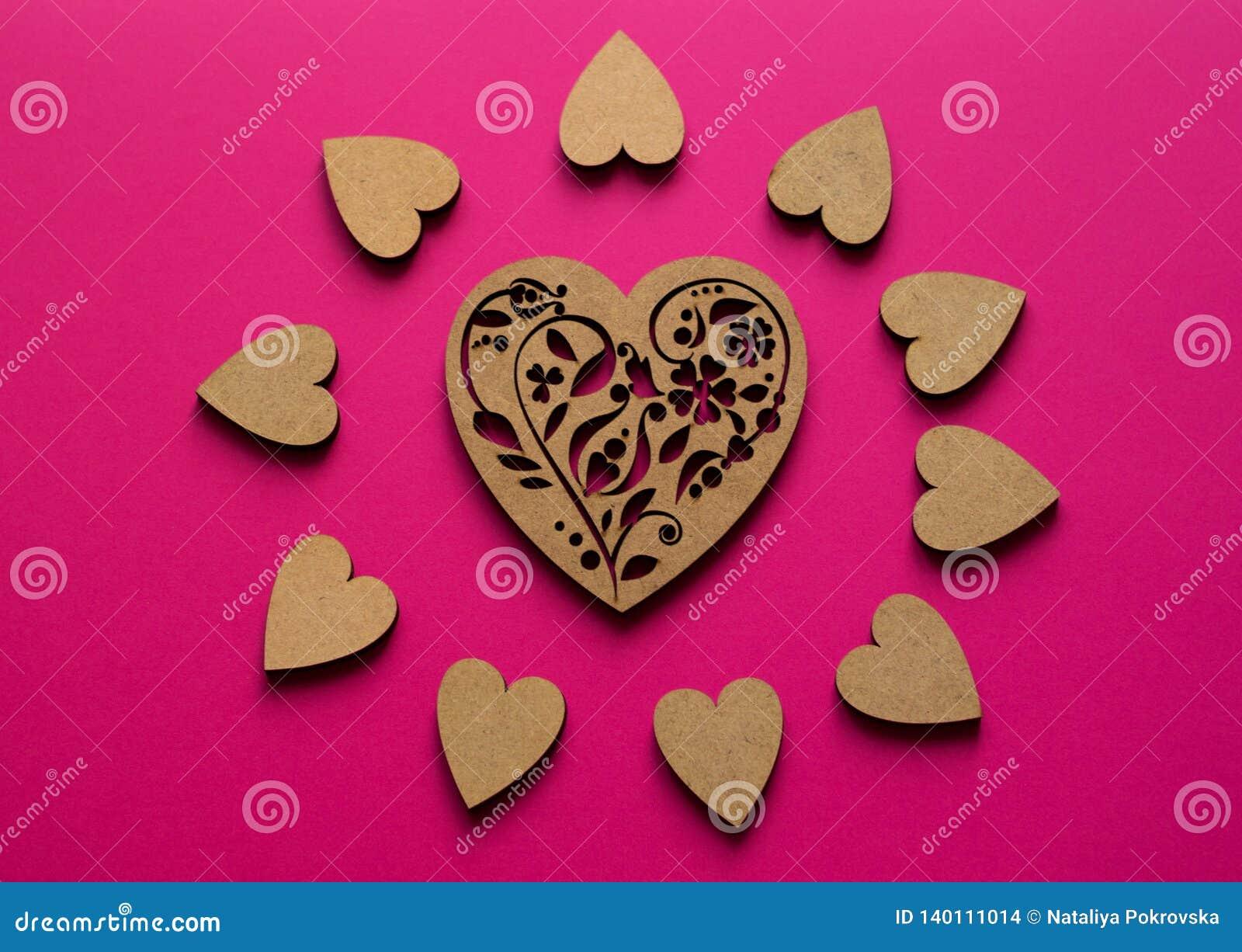 Zonnige hartensamenstelling van hoogste mening over roze achtergrond Pook-trekkend houten hart in het centrum