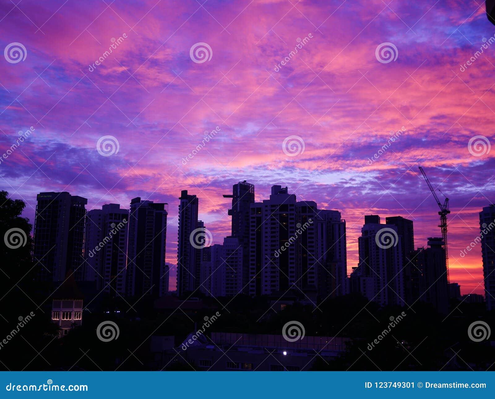 Zonsondergang achter gebouwen met mooie bewolkte hemel