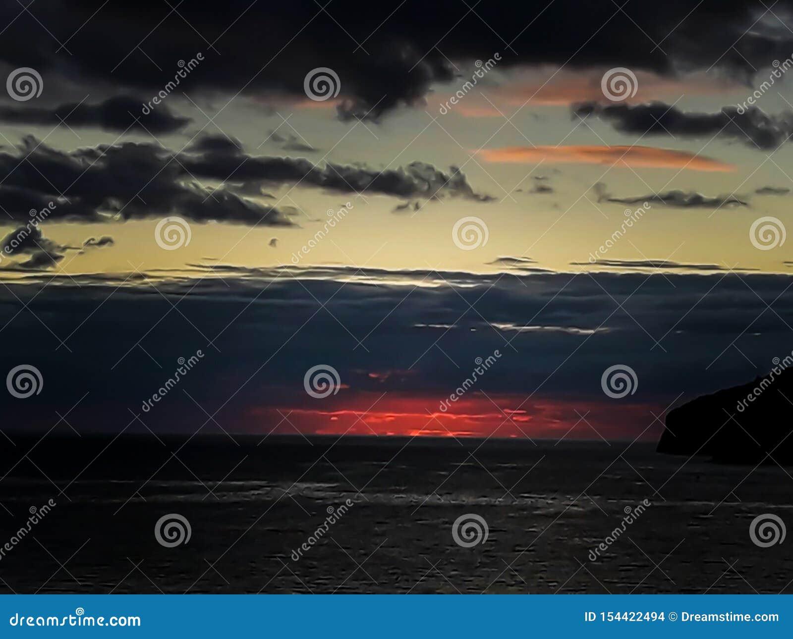 Zonsondergang bij het overzees met toneelwolken op de horizon