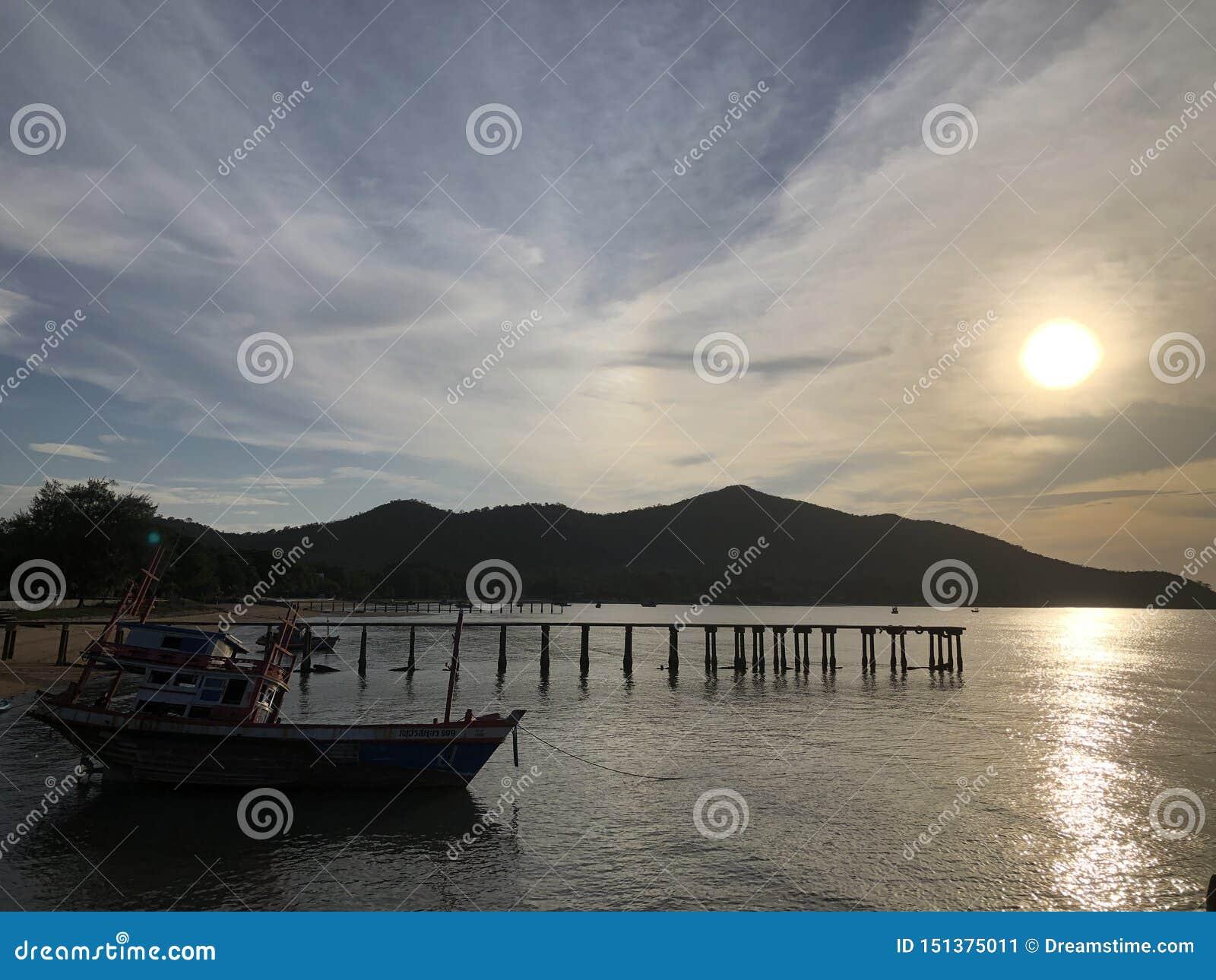 Zonsondergang bij het strand in Thailand met bootsilhouet