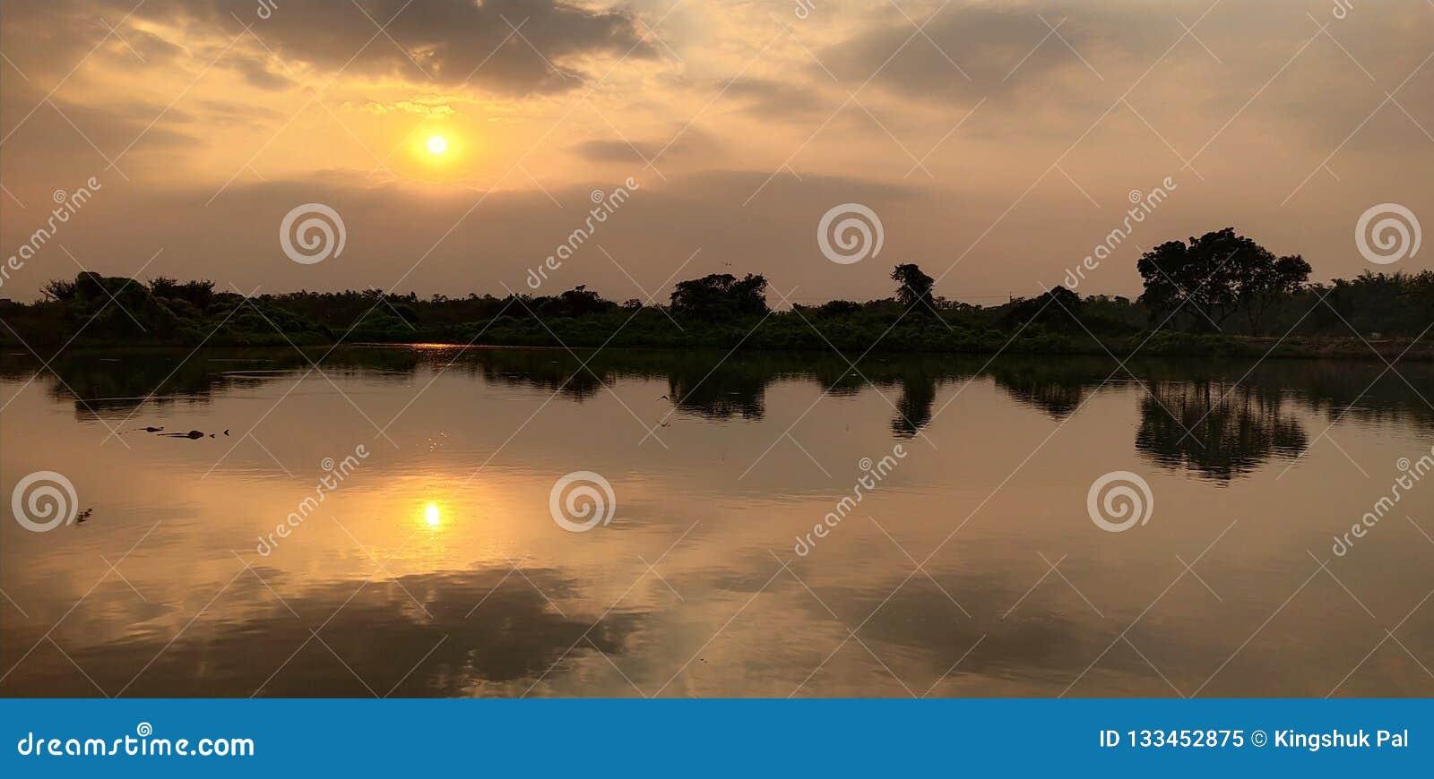 Zonsondergang bij oever van het meer