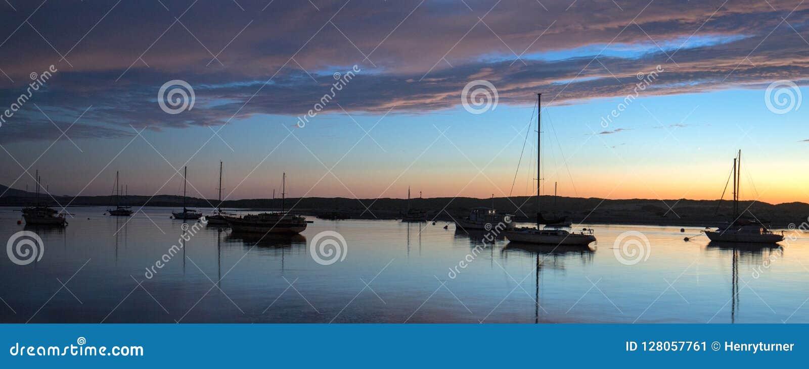 Zonsondergang bij schemering over Morro-de boten van de Baaihaven en Morro-Rots op de centrale kust van Californië in Californië