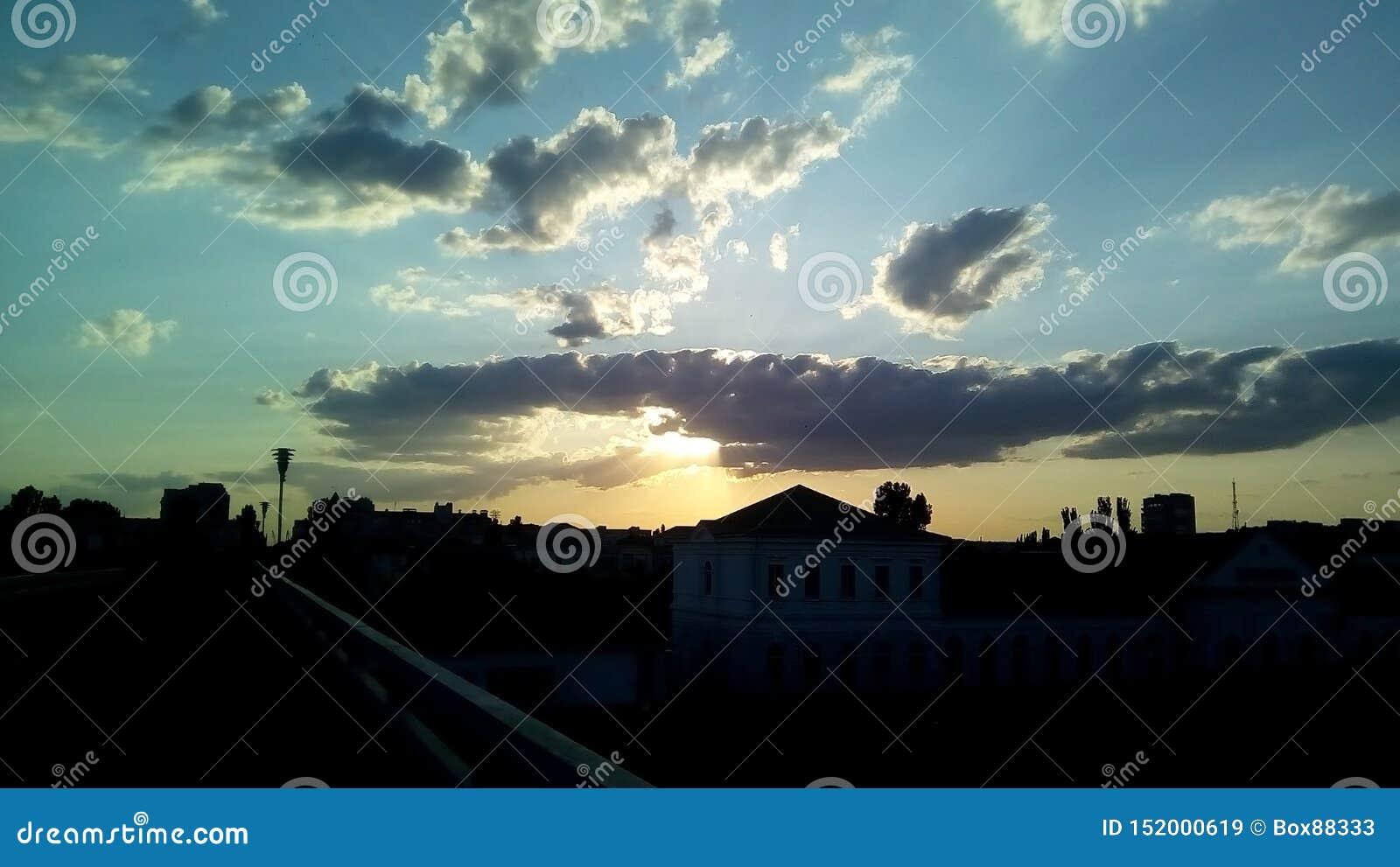 Zonsondergang in de stad Donkere silhouetten van gebouwen tegen de avondhemel