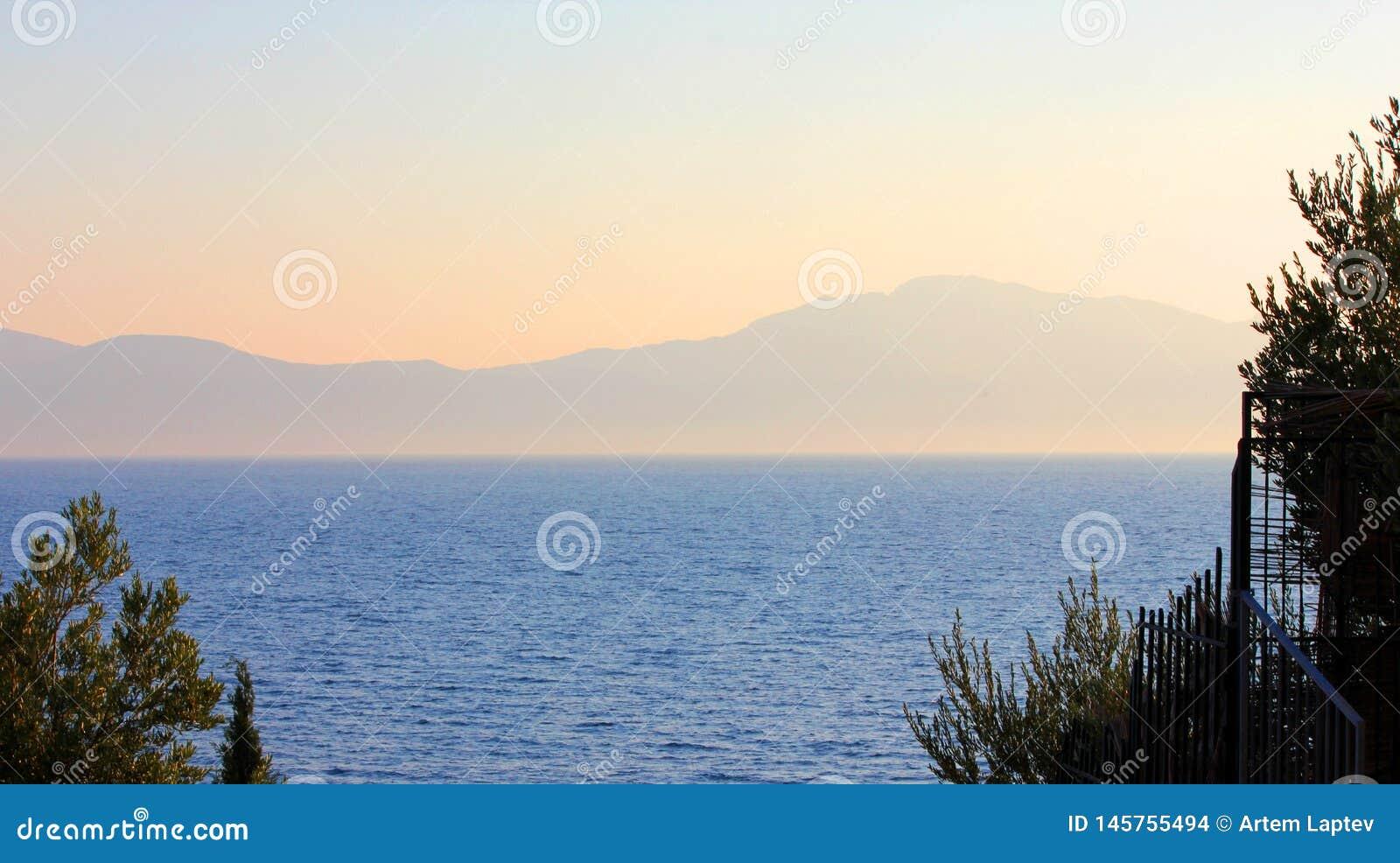 Zonsondergang die het overzees en de bergen overziet