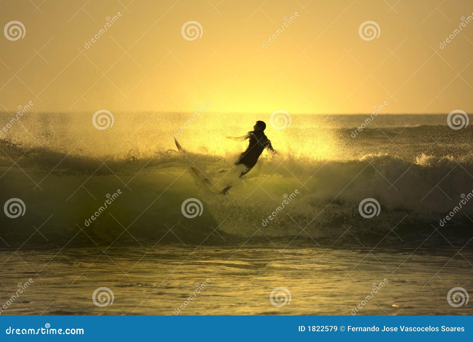 Zonsondergang die surfer valt