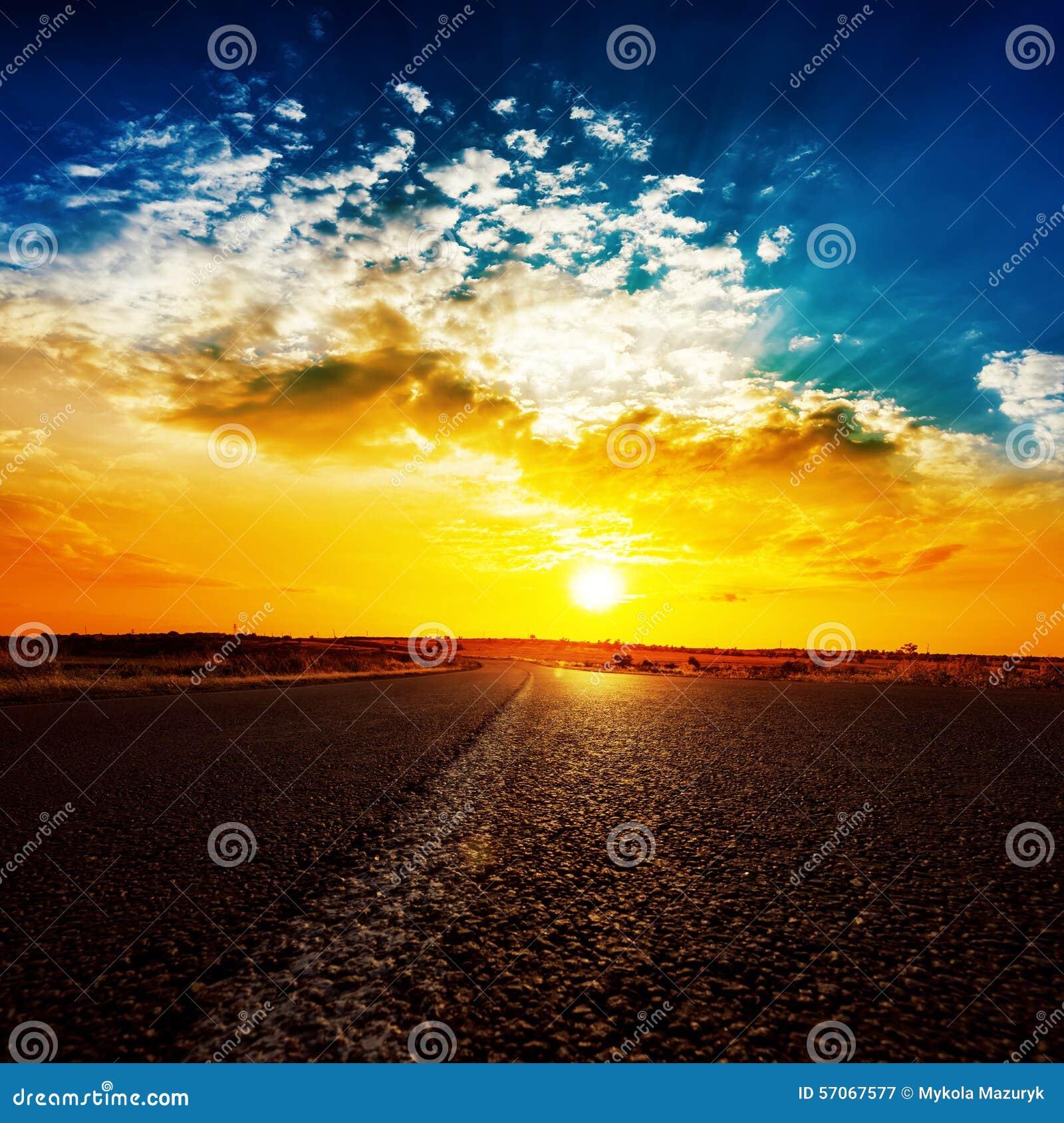 Zonsondergang en asfaltweg aan horizon