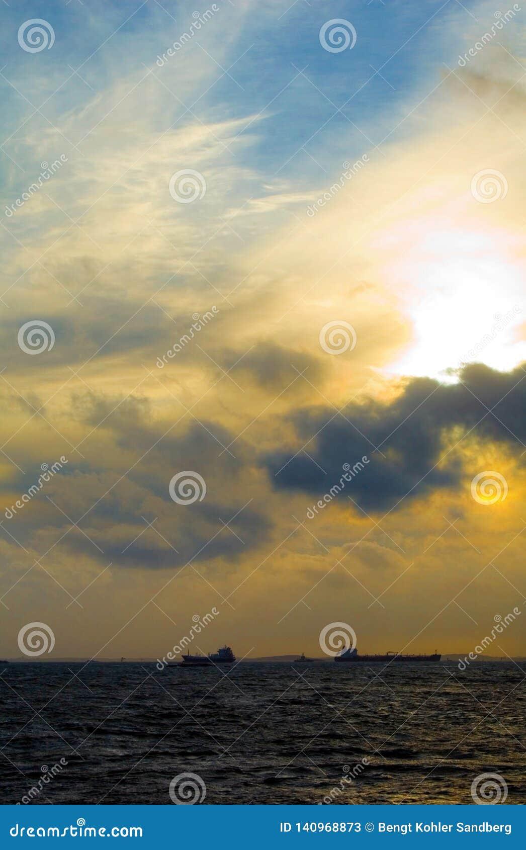 Zonsondergang met schepen op de horizon