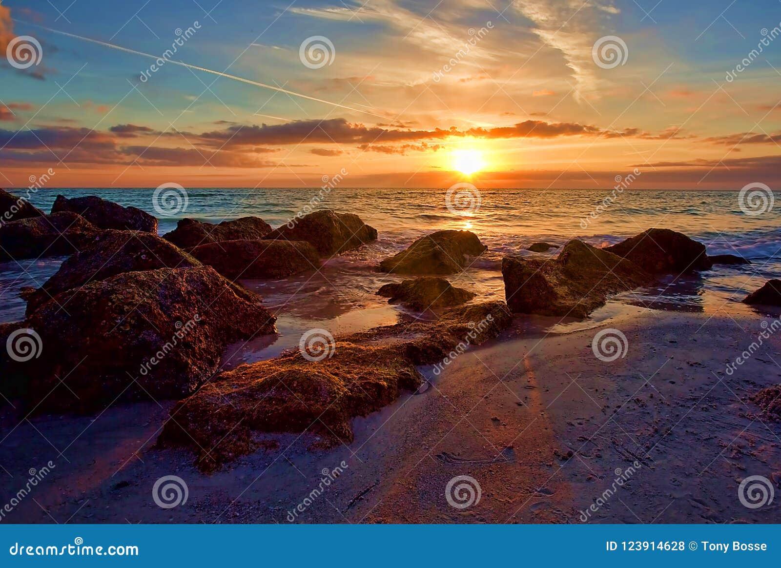 Zonsondergang met Zonnestraal over Rocky Seashore