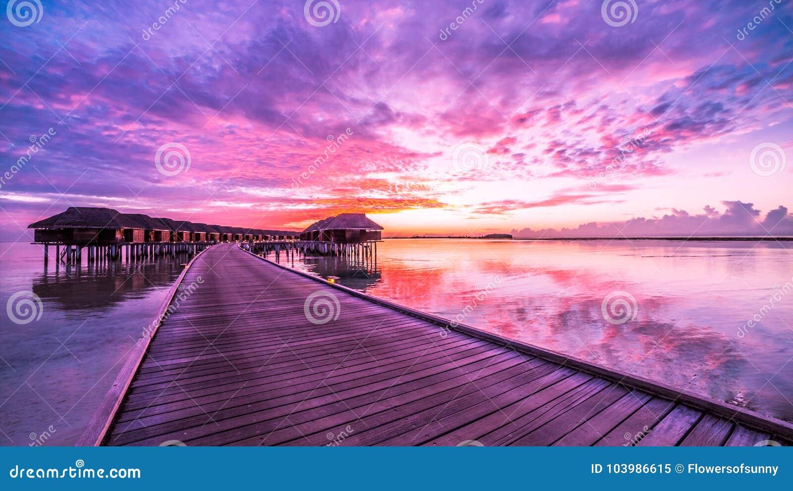 Zonsondergang op het eiland van de Maldiven, de villa stoevlucht van het luxewater en houten pijler Mooie hemel en wolken en de a