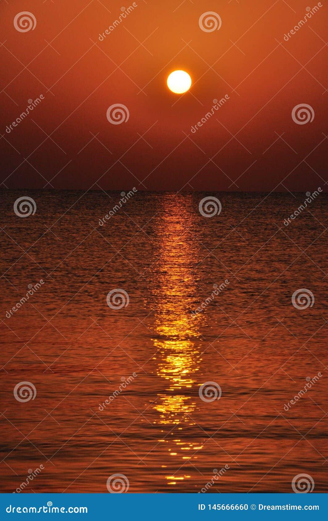 Zonsondergang over de overzeese oppervlakte met bezinningen van stralen op de oppervlakte