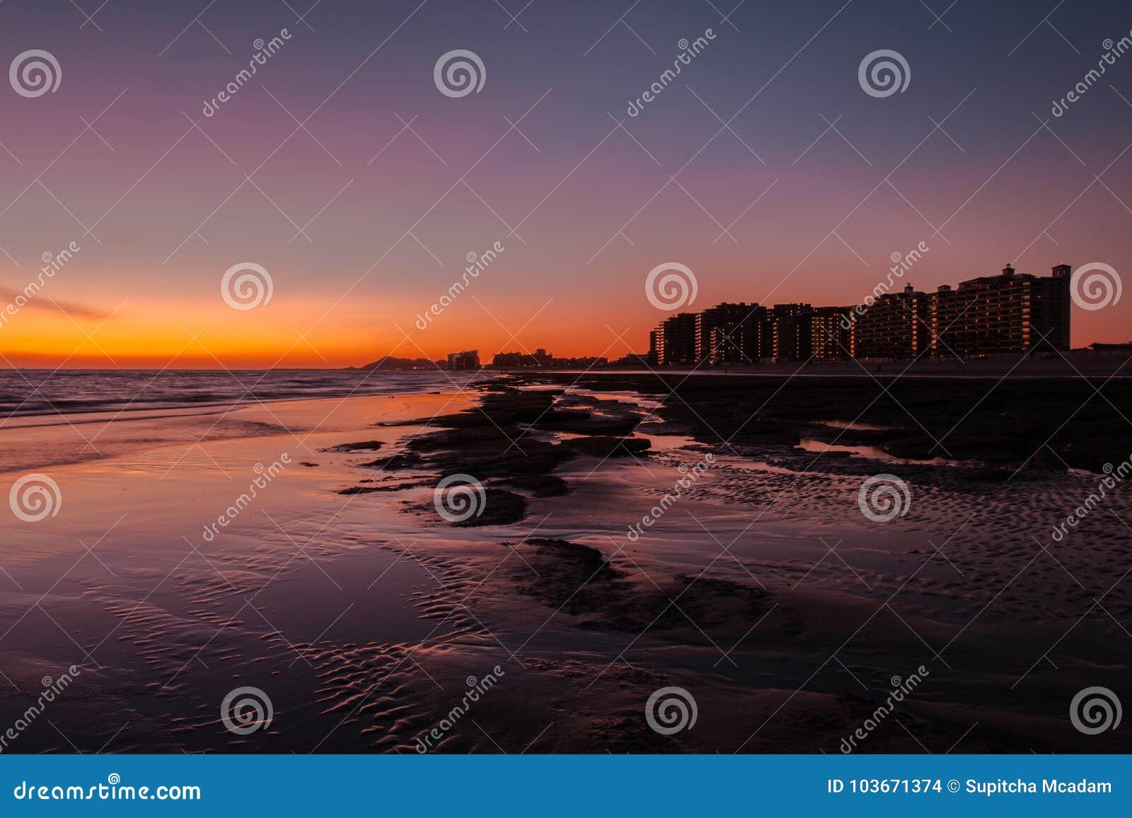 Zonsondergang over een rotsachtig strand vooraan de hotels