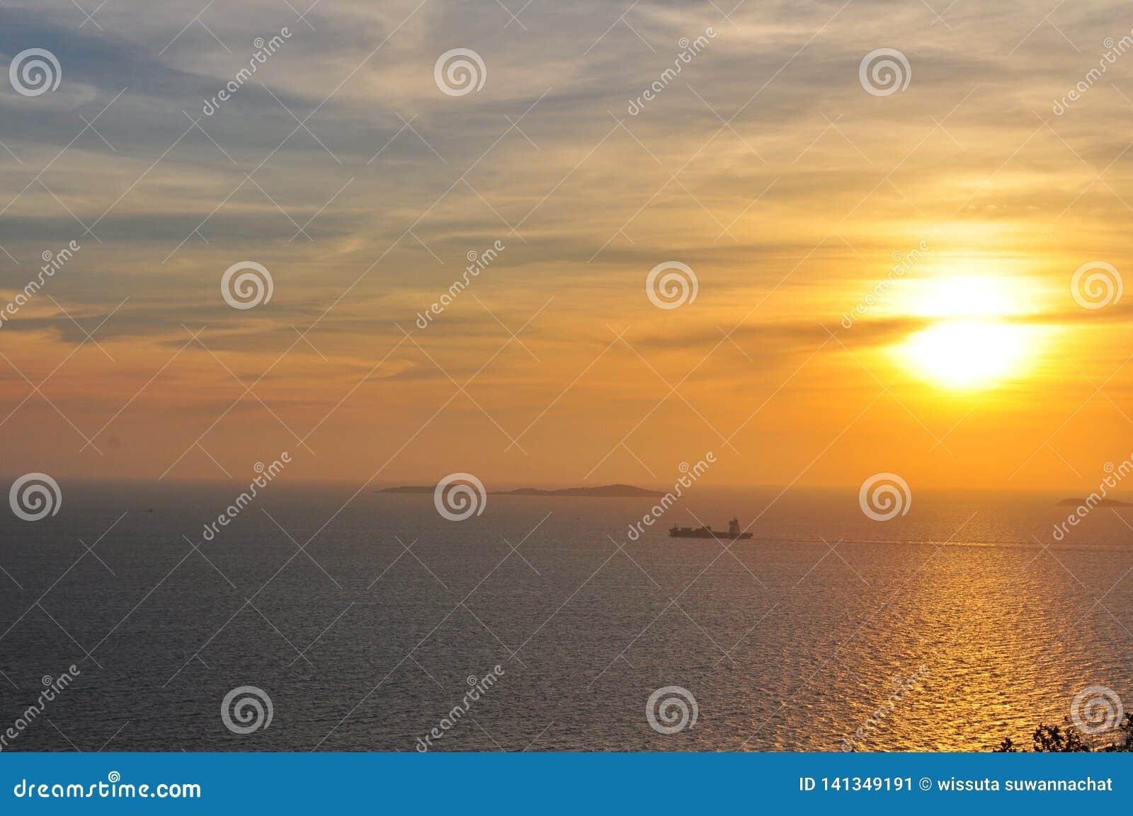 Zonsondergang over het overzees met een boot op de achtergrond