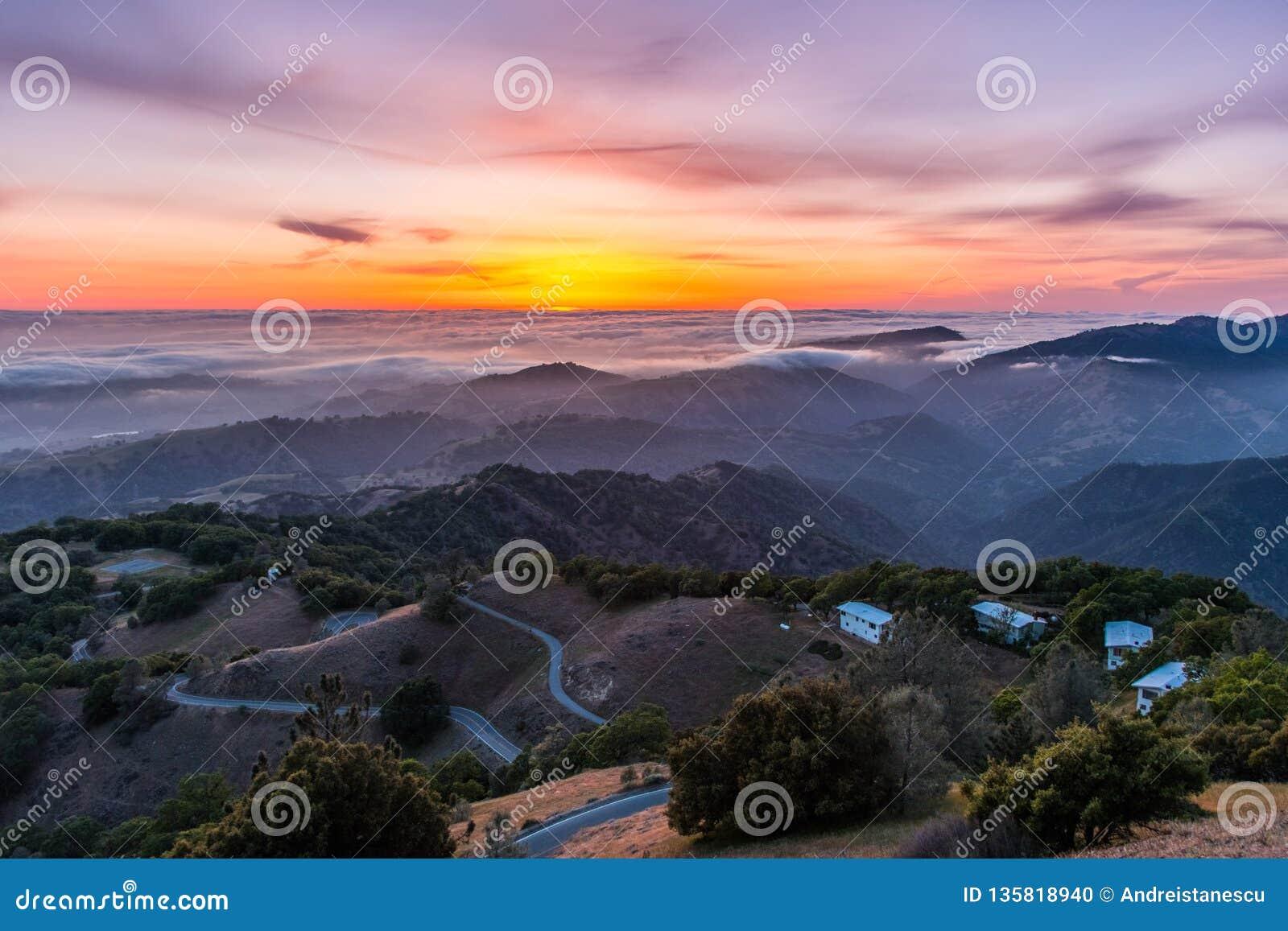 Zonsondergangnagloeiing over een overzees van wolken; windende weg die door rollende heuvels in de voorgrond dalen; MT Hamilton,