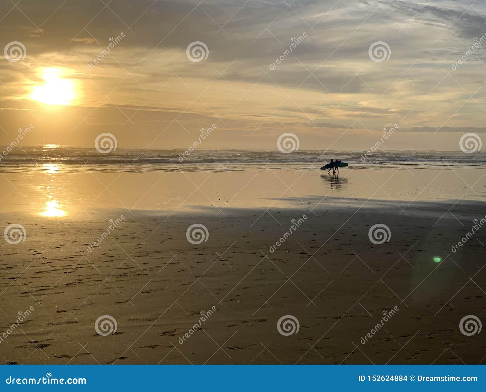 Zonsondergangsurfers bij het strand