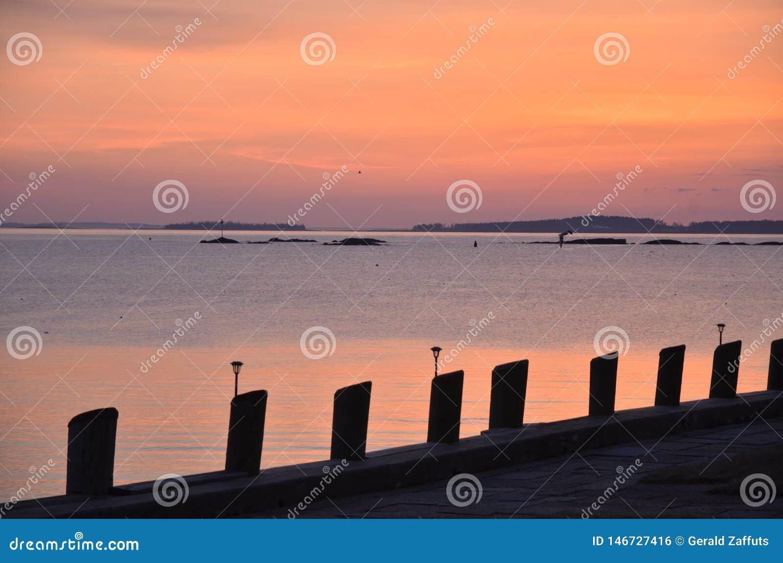 Zonsopgang over de oceaan met silhouet van pijler