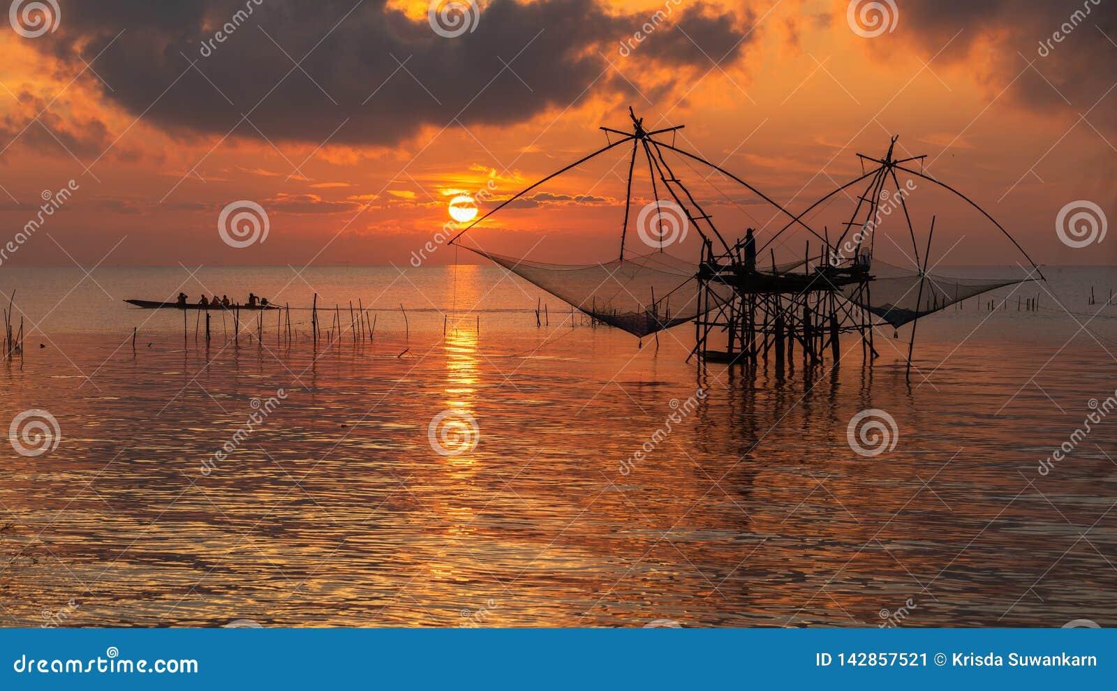 Zonsopganghemel met visser op vierkante onderdompeling netto en toerismeboot bij Pakpra-dorp