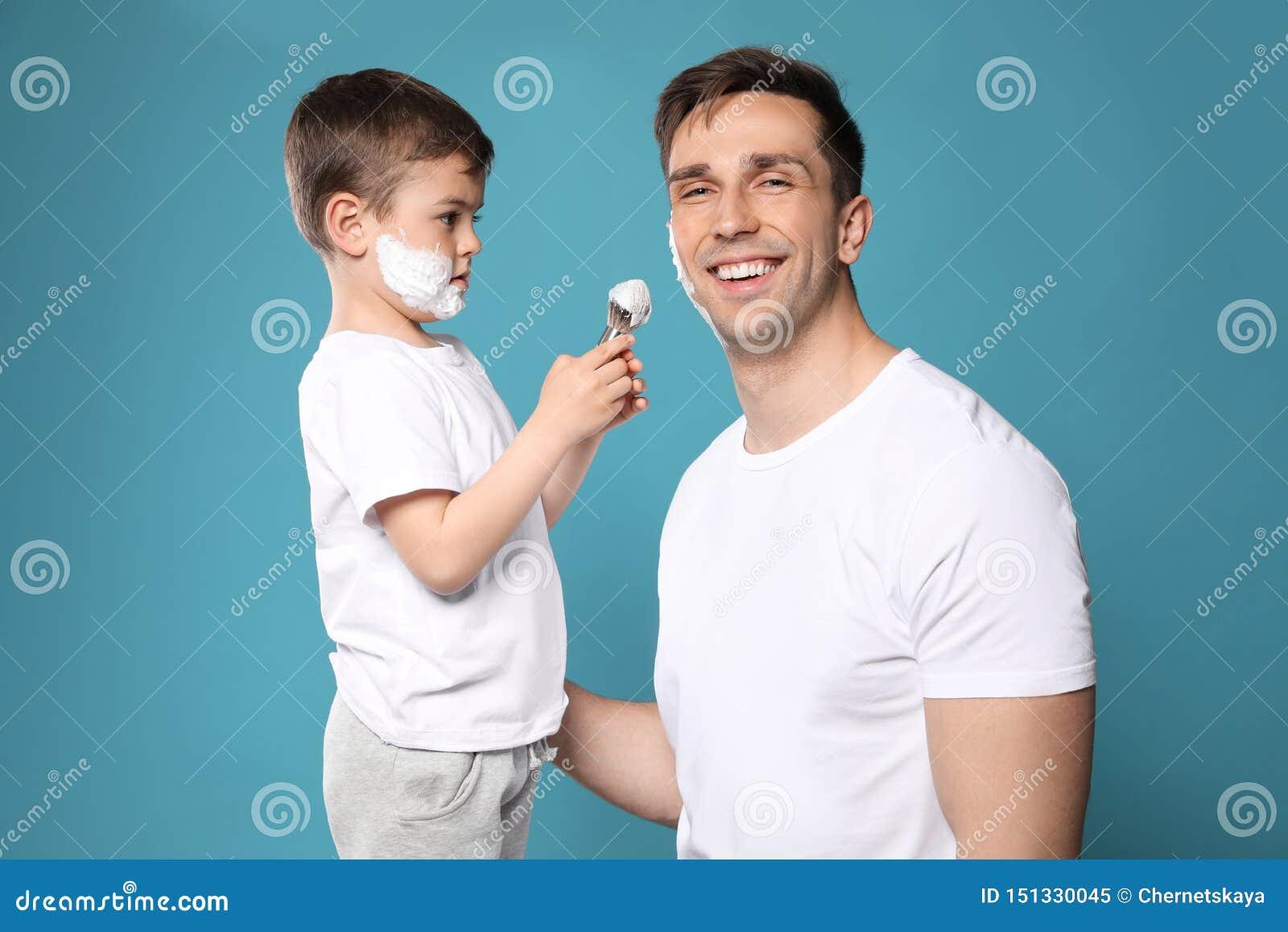 Zoon die het scheren schuim op het gezicht van de papa toepassen